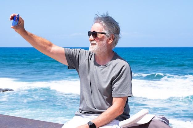 Uśmiechnięty starszy mężczyzna z brodą siedzący na morzu robiący selfie z telefonem komórkowym, cieszący się wolnością i wakacjami