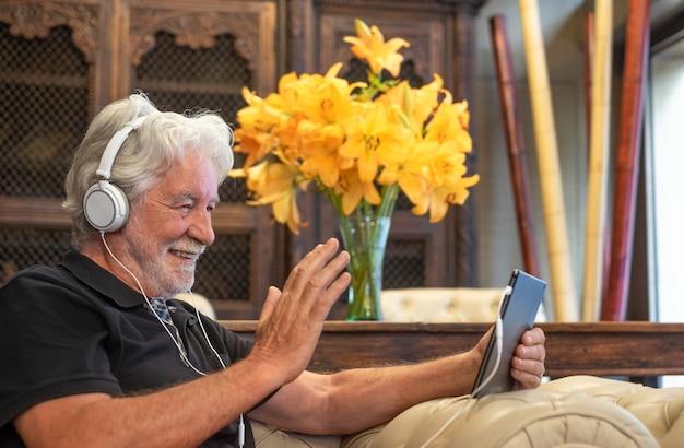 Uśmiechnięty starszy mężczyzna za pomocą urządzenia elektronicznego ze słuchawkami w rozmowie wideo. siedząc w fotelu