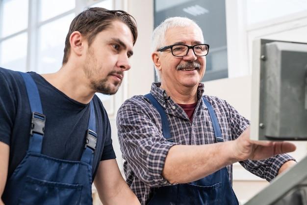 Uśmiechnięty starszy pracownik z wąsami omawiający konfiguracje maszyny fabrycznej z młodym kolegą w warsztacie