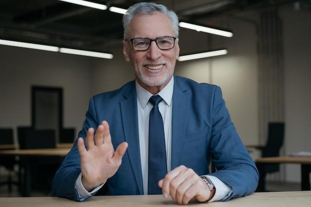 Uśmiechnięty starszy trener biznesu o połączenie wideo, mówi do kamery. koncepcja spotkania online