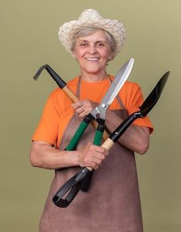 Uśmiechnięty starszy żeński ogrodnik na sobie kapelusz ogrodniczy posiadający narzędzia ogrodnicze na oliwkowej zieleni