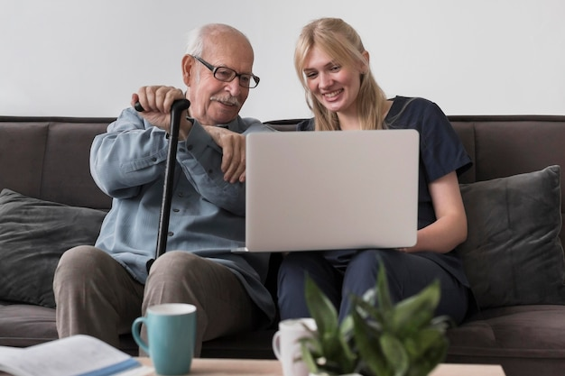 Uśmiechnięty staruszek i pielęgniarka za pomocą laptopa