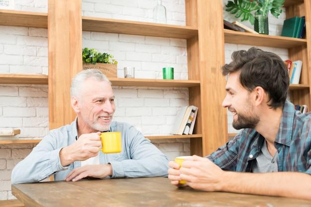 Uśmiechnięty starzejący się mężczyzna i szczęśliwy młody facet z filiżankami przy stołem