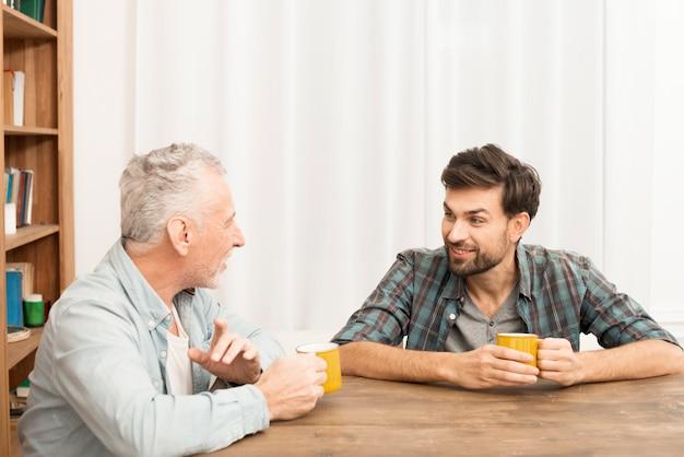Uśmiechnięty starzejący się mężczyzna i szczęśliwy młody facet z kubkami przy stołem