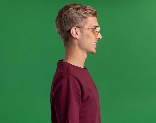 Uśmiechnięty stojący w widoku profilu młody przystojny facet w czerwonej koszuli i okularach odizolowanych na zielonej ścianie z kopią przestrzeni