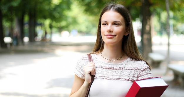 Uśmiechnięty studencki plenerowy mienie książka