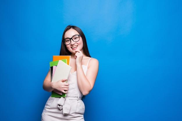 Uśmiechnięty student azjatyckich kobieta trzymając książki i plik, student college'u lub szkoły i koncepcja edukacji na białym tle na niebieskiej ścianie z miejsca na kopię.