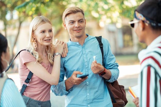Uśmiechnięty student stojący ze swoją dziewczyną przed kolegami z grupy