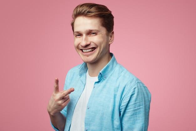 Uśmiechnięty student ubrany w niebieską koszulę i pokazujący znak vsign przez różową ścianę