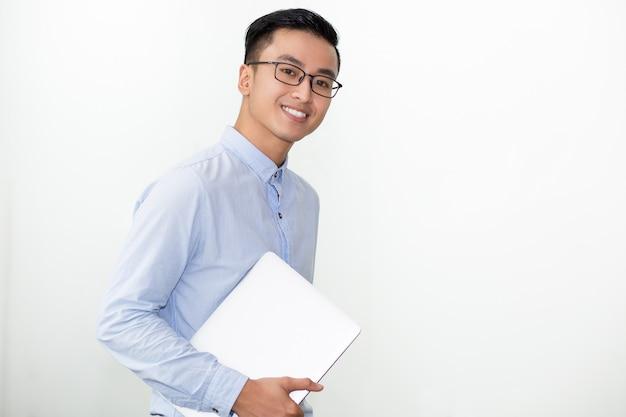 Uśmiechnięty student w okularach przewożących laptopa