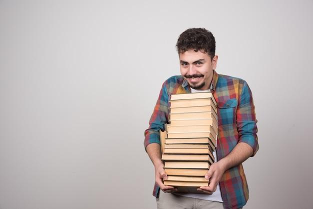 Uśmiechnięty student z stosem książek patrząc na kamery.