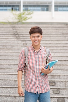 Uśmiechnięty student ze swoimi książkami na uniwersytecie