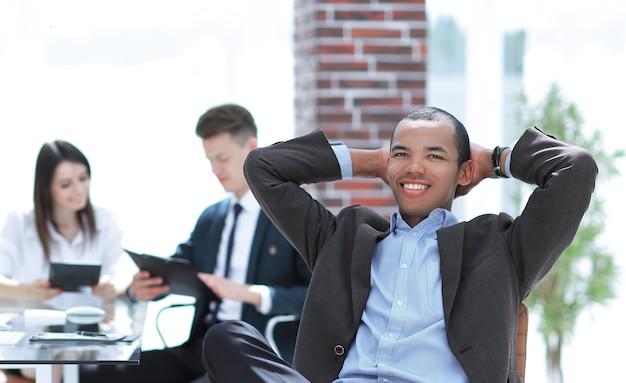 Uśmiechnięty sukcesy biznesmen siedział na krześle biurowym