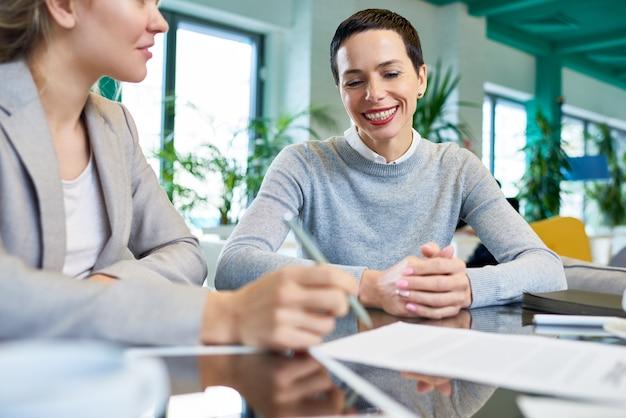 Uśmiechnięty sukcesy bizneswoman rozmawia z partnerem