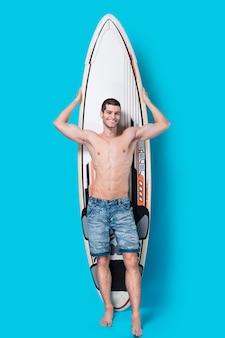 Uśmiechnięty surfingowiec trzyma surfboard