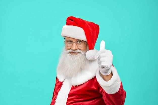 Uśmiechnięty święty mikołaj pokazuje kciuk do góry.