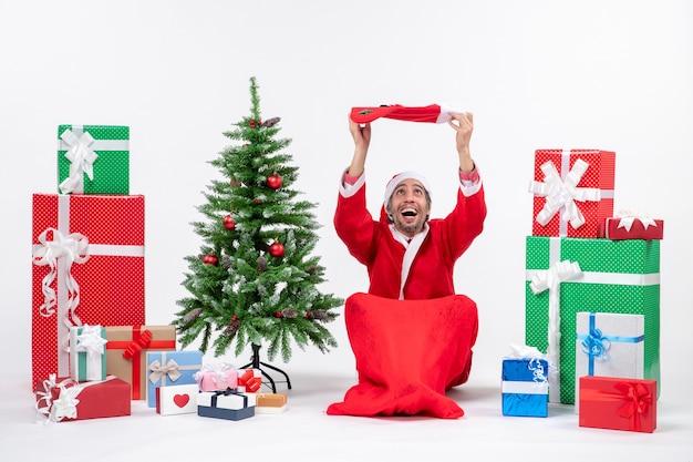Uśmiechnięty święty mikołaj siedzi na ziemi i podnosi skarpetę bożonarodzeniową na głowę w pobliżu prezentów i udekorowane drzewo noworoczne na białym tle