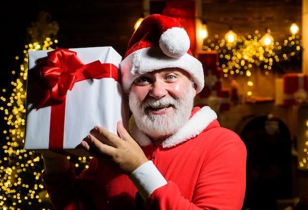 Uśmiechnięty święty mikołaj trzyma pudełko prezentowe święty mikołaj trzyma prezent noworoczny świąteczna dekoracja wesołych