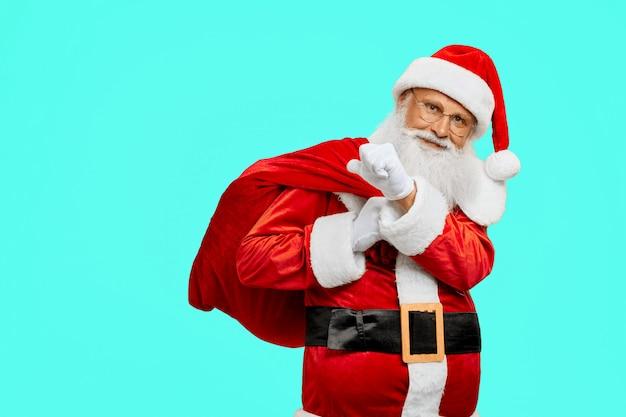 Uśmiechnięty święty mikołaj trzyma worek z prezentami.