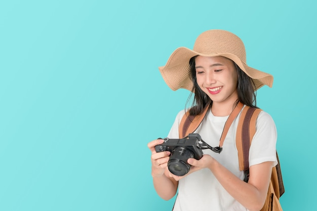 Uśmiechnięty szczęśliwie azjatycki kobieta podróżnika mienia kamera i spojrzenie fotografia na błękitnym tle.