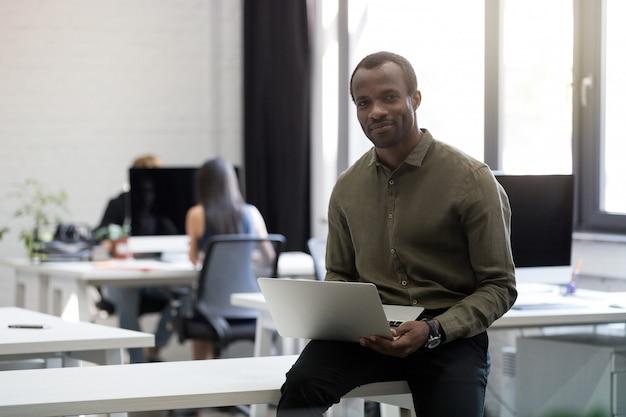 Uśmiechnięty szczęśliwy afro amerykański biznesmena obsiadanie na jego biurku