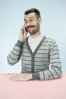 Uśmiechnięty szczęśliwy biznesowy mężczyzna rozmawia przez telefon siedzi przy stole. pojęcie męskich emocji
