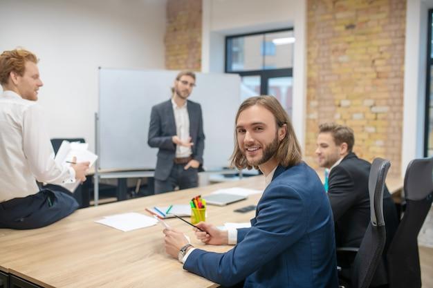 Uśmiechnięty szczęśliwy człowiek w niebieskiej kurtce, zwracając się do aparatu i kolegów komunikujących się po prezentacji