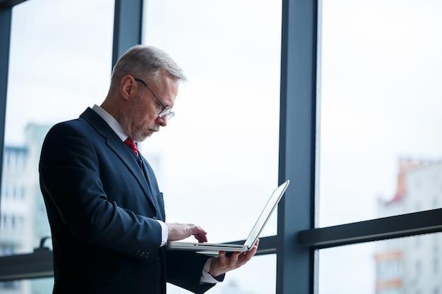 Uśmiechnięty szczęśliwy dyrektor zarządzający myśli o pomyślnym rozwoju kariery, stojąc z laptopem w swoim biurze w pobliżu okna z miejscem na kopię