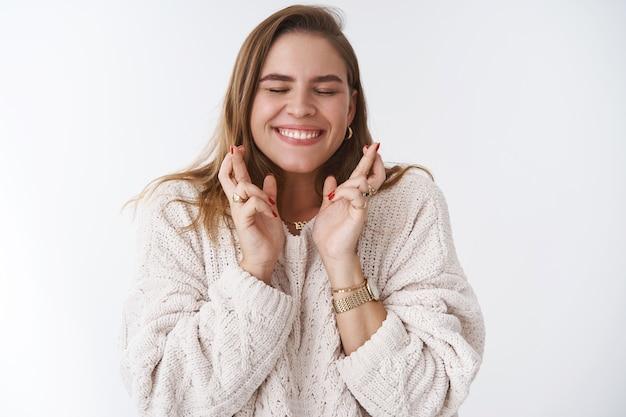 Uśmiechnięty szczęśliwy entuzjastyczny podekscytowany przystojna dziewczyna czekająca ważna wiadomość uniwersytet uśmiechnięty szeroko składanie życzeń krzyże palce powodzenia zamknij oczy zachwycony oczekując spełnienia marzeń