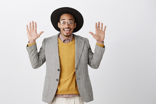 Uśmiechnięty szczęśliwy i zaskoczony afroamerykanin facet podnosząc ręce