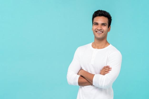 Uśmiechnięty szczęśliwy indyjski mężczyzna z rękami skrzyżowanymi