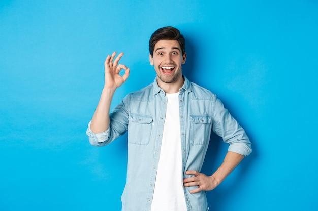 Uśmiechnięty szczęśliwy mężczyzna pokazujący znak ok i wyglądający na zadowolonego, aprobujący coś dobrego, stojący na niebieskim tle.