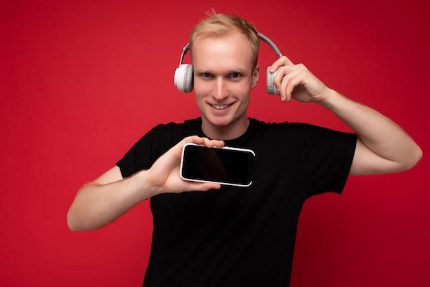 Uśmiechnięty szczęśliwy przystojny blond młody facet ubrany w czarną koszulkę i białe słuchawki, stojący na białym tle nad czerwonym tle z kopią przestrzeni trzymającej smartfon i pokazujący ekran telefonu komórkowego, słuchając