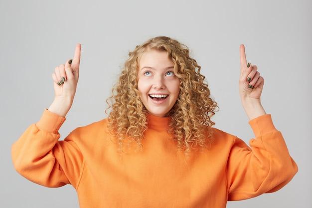 Uśmiechnięty szczęśliwy zadowolony blondynki dziewczyna, będąc zaskoczonym, patrząc i pokazując w górę palcami wskazującymi