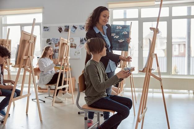 Uśmiechnięty szczęśliwy żeński nauczyciel rasy mieszanej patrzy na pracę rysunkową ucznia