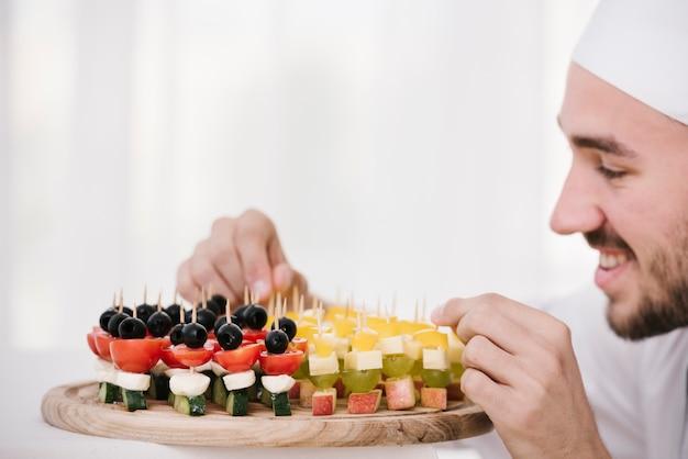 Uśmiechnięty szef kuchni organizuje talerz przekąsek