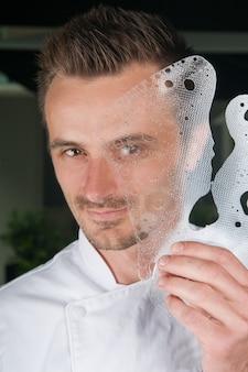 Uśmiechnięty szef kuchni trzyma dekoracyjną lodową płytkę przed jego twarzą
