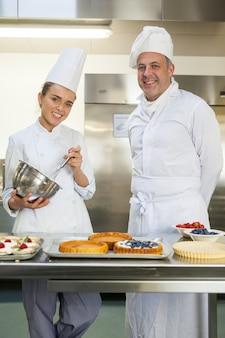 Uśmiechnięty szef kuchni trzyma trzepaczka podczas gdy oglądający kierowniczym szefem kuchni