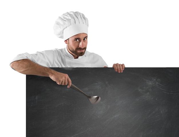 Uśmiechnięty szef kuchni z kadzią wskazuje deskę