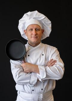 Uśmiechnięty szef kuchni z kapeluszem trzymając patelnię