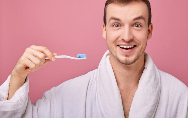 Uśmiechnięty szeroko mężczyzna w białej szacie ze szczoteczką do zębów szczęśliwy
