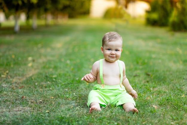 Uśmiechnięty sześciomiesięczny chłopiec siedzący latem na zielonym trawniku w krótkich spodenkach o zachodzie słońca, miejsce na tekst
