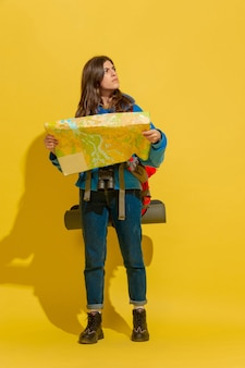 Uśmiechnięty, szukający drogi. portret wesoły młody turysta kaukaski dziewczyna z torbą i lornetką na białym tle na żółtym tle studio. przygotowanie do podróży. ośrodek wypoczynkowy, ludzkie emocje, wakacje.