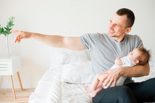 Uśmiechnięty tata trzyma dziecka podczas gdy wskazujący daleko od