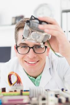 Uśmiechnięty technik pracuje na łamanej jednostce centralnej