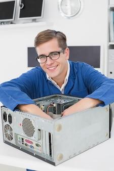 Uśmiechnięty technik pracuje na łamanym komputerze