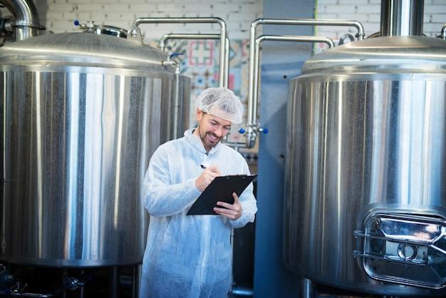 Uśmiechnięty technolog robi notatki na linii produkcyjnej fabryki zadowolony z wyników