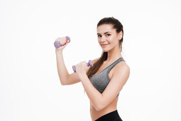 Uśmiechnięty trening kobiety fitness z małymi hantlami na białym tle