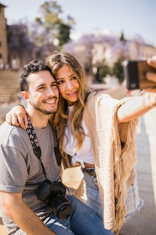 Uśmiechnięty turysta bierze jaźń portret na telefonie komórkowym
