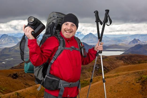 Uśmiechnięty turysta mężczyzna w czerwonej kurtce z aparatem w ręku